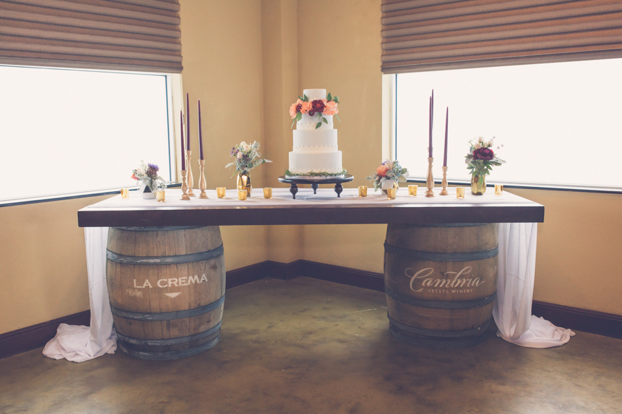 Modern Rustic Wedding Dessert Table on Antique Barrels, with 4 Tier Round White Wedding Cake with Peach and Bordeaux Roses with Greenery, with Tall Burgundy Candles in Gold Candleholders, and Peach and Red Flowers with Sage Greenery in Gold Geodesic Vases | Tampa Bay Wedding Reception Venue Crowne Plaza Tampa