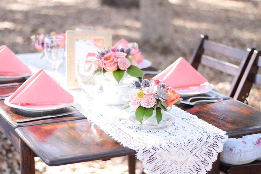 Outdoor Park Wedding Reception Table Decor with Lace Runner, Low Blush, Peach, Thistle and Succulent with Greenery Centerpiece, Framed Table Number, Vintage Wood Table and Folding Chairs with Floral Cushions, and Coral Napkins