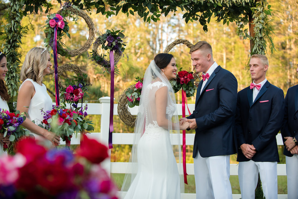 Outdoor Southern Wedding Ceremony Portrait with Greenery Garland Arch, and Hanging Woven Branch Wreaths with Purple, Magenta, and Red Roses with Ribbon | Groomsmen in Navy Suit Jackets in Hot Pink Bow Ties with White Pants | Tampa Bay Wedding Photographer Caroline & Evan Photography | Lutz Florida Wedding Venue Southern Plantation Oasis | Northside Florist | Wedding Planner Exquisite Events