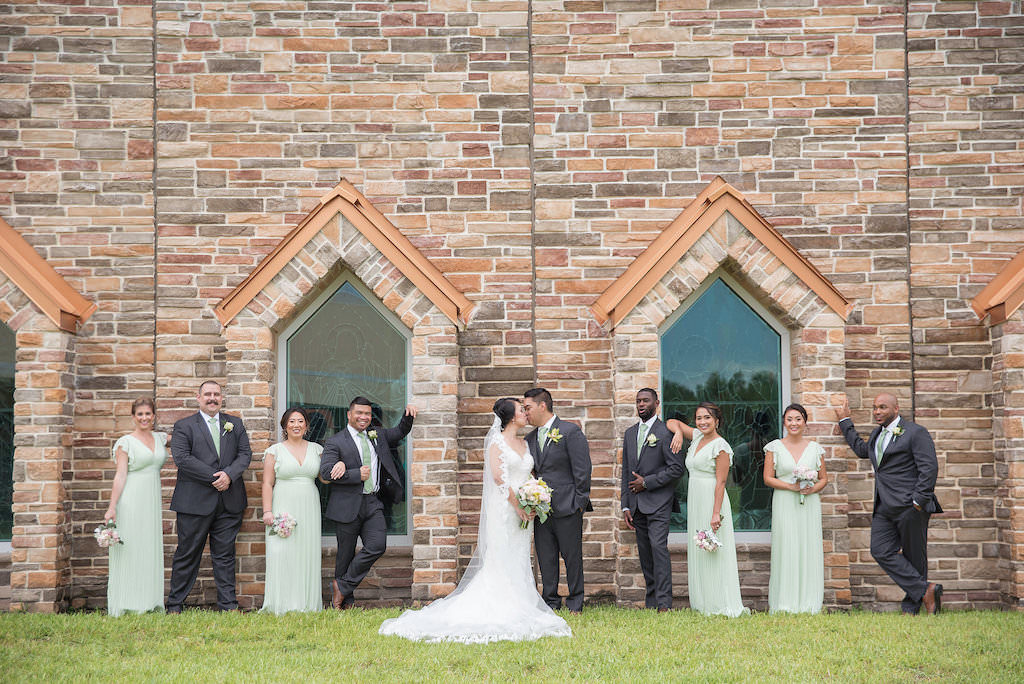 Outdoor Wedding Party Portrait with Church Windows, Bride in V Neck Stella York Wedding Dress, Bridesmaids in Floor Length V Neck Light Green Dresses, Groomsmen with Light Green Ties and Yellow Boutonnieres | Tampa Bay Wedding Photographer Kristen Marie Photography