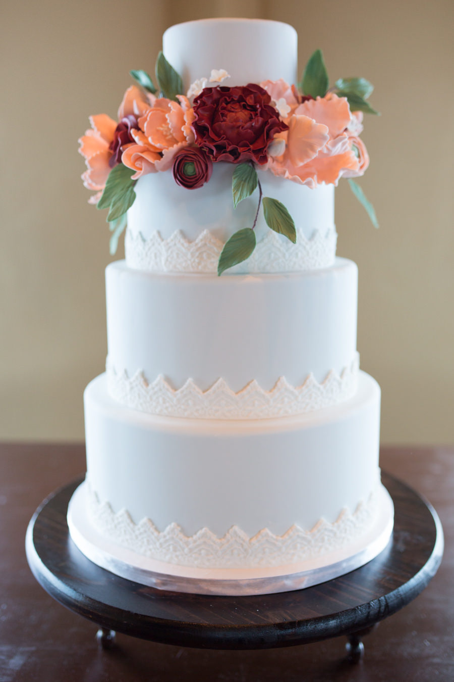 Four Tiered Round Light Blue with Triangle Lace Pattern Wedding Cake on Dark Wood Cake Stangd, with Peach and Burgundy Rose with Greenery Flowers