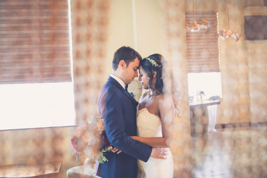 Bride and Groom First Dance Portrait, Bride with Small Floral Headband Hair Accessory and Peach and Burgundy Bouquet, Groom in Blue Suit