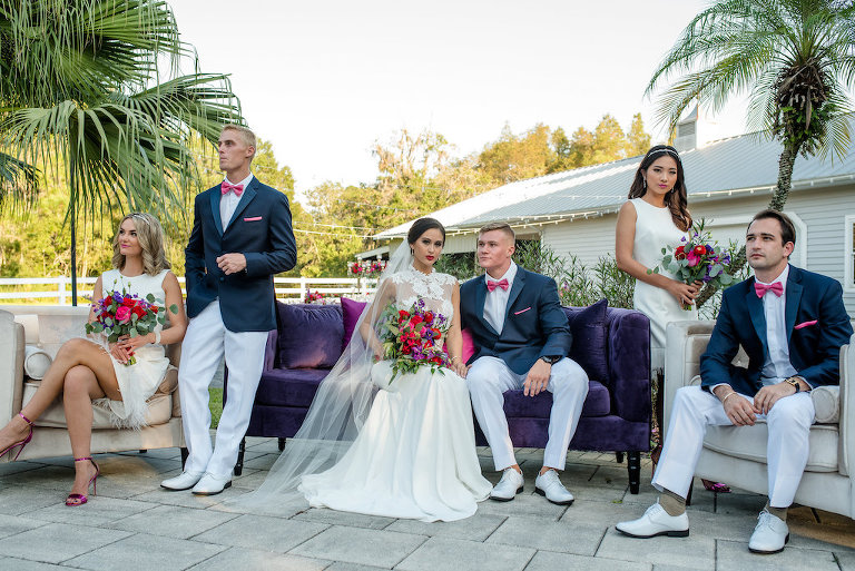 Retro Southern Inspired Wedding Party Outdoor Patio Portrait, Groomsmen in Navy Jackets, White Pants and Shoes, and Hot Pink Bow Ties | Red and Purple with Greenery Bouquet from Northside Florist | Classic Bridesmaids Dresses Truly Forever Bridal | Daalarna Couture Illusion Lace Wedding Dress from The Bride Tampa | Lutz Florida Wedding Venue Southern Plantation Oasis | Tampa Wedding Planner Exquisite Events | Caroline & Evan Photography