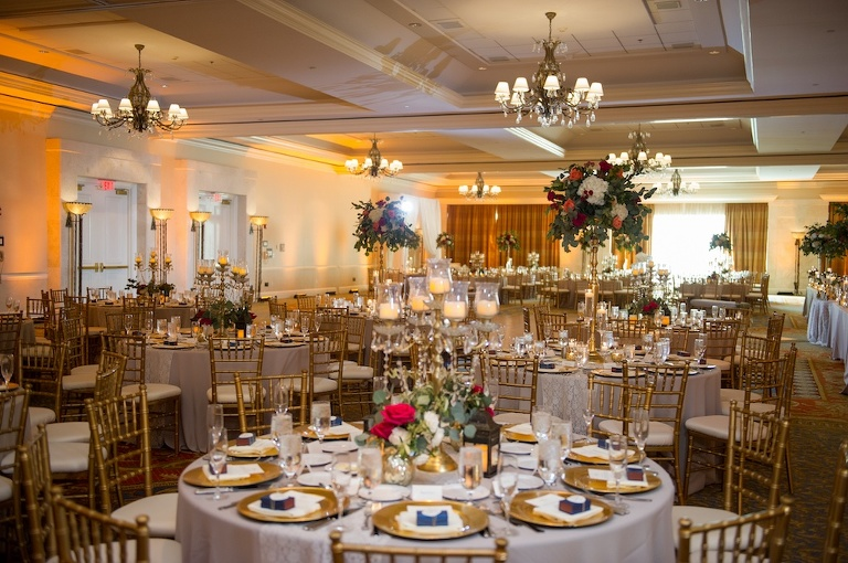 Old Florida Inspired Ballroom Wedding Reception with Navy Blue Favors, Gold Chargers and Chiavari Chairs, and Tall Gold and Glass Candle Lantern Antique Candelabra Red Rose with White Hydrangea and Greenery Centerpiece | Downtown Tampa Hotel Wedding Venue Tampa Marriott Waterside