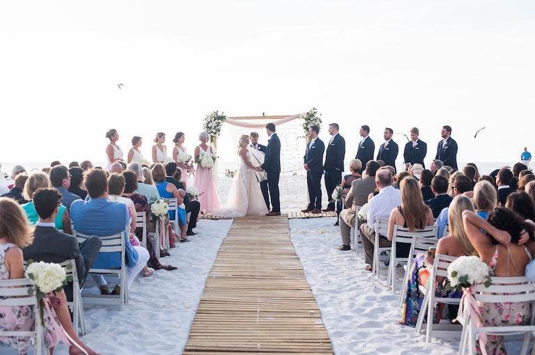 Boho Florida Beach Wedding Ceremony With Bamboo Aisle White Folding Chairs Hydrangeas And