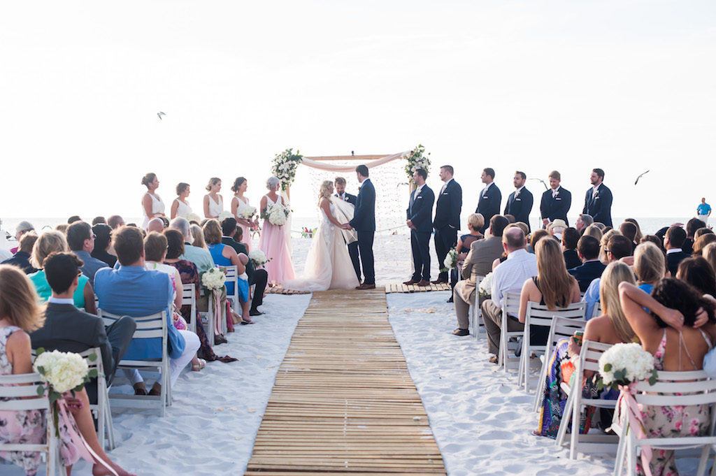 Boho Florida Beach Wedding Ceremony with Bamboo Ceremony Aisle, White Folding Chairs with Hydrangeas and Blush Ribbon, and Floral Bamboo Arch, Groomsmen in Navy Suits | Destination Hotel Wedding Venue Hilton Clearwater Beach