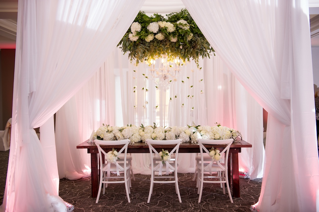 Elegant Southern White Wedding Reception Decor with Suspended White Florals with Hanging Organic Greenery, Low White Hydrangea Table Runner Garland Centerpiece, and White X Back Chairs with White Flowers and Ribbon at Wooden Farmhouse Table | Tampa Bay Wedding Planner Love Lee Lane | Tampa Event Rentals and Florist Gabro Event Services | Wedding Rentals A Chair Affair