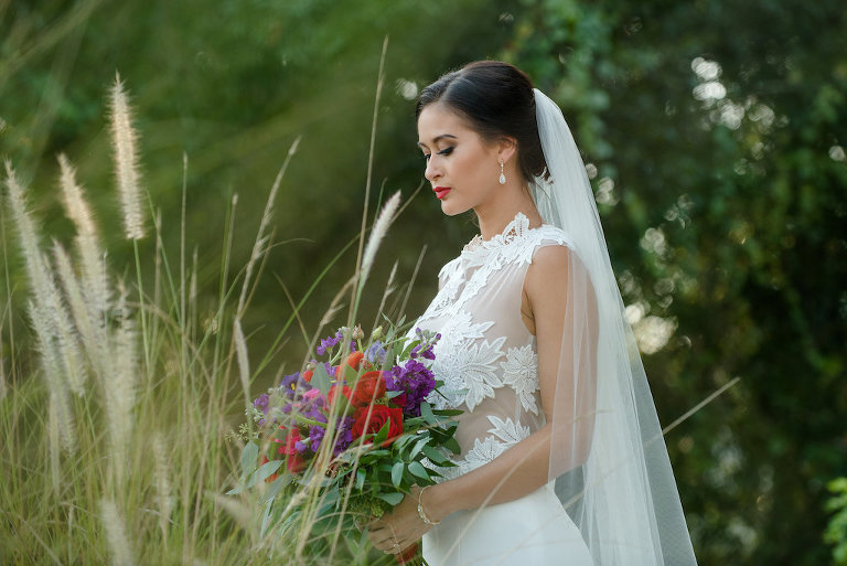 Outdoor Bridal Portrait in Floral Lace Cutout Wedding Dress with Red, Purple, and Greenery Bouquet | Tampa Bay Dress Boutique The Bride Tampa | Photography by Caroline & Evan Photography | Hair and Makeup Michele Renee The Studio