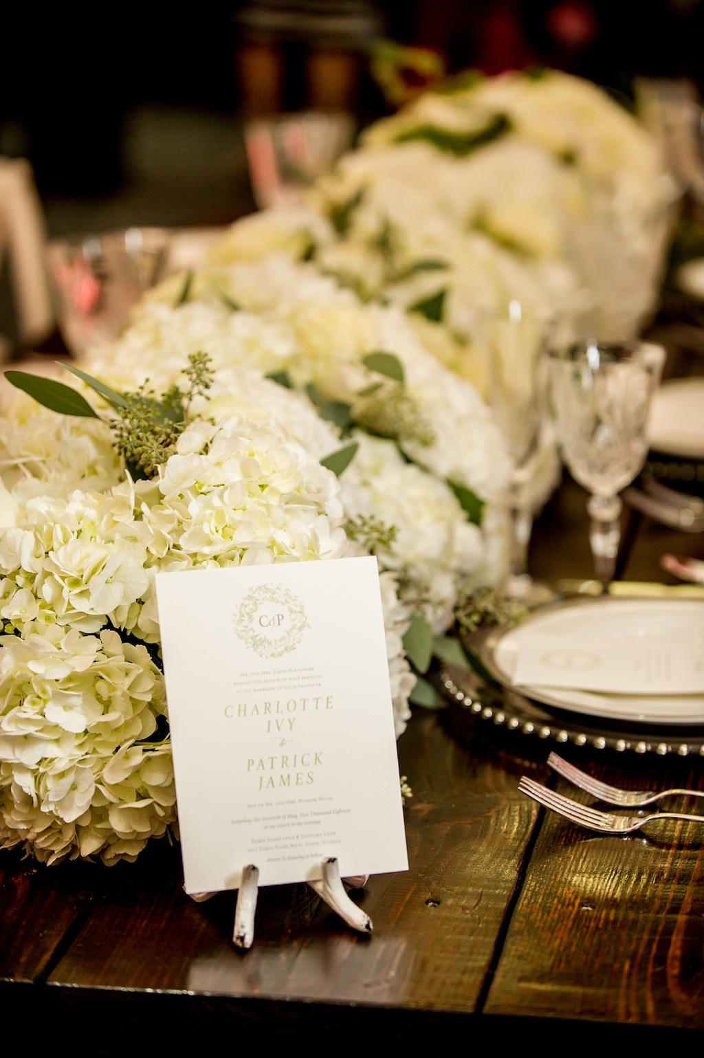 Elegant Southern Wedding Reception Table Decor Details with White Hydrangea with Greenery Garland Centerpiece on Natural Wood Farmhouse Table, and Green Floral and White Wedding Program | Tampa Bay Wedding Planner Love Lee Lane | Tampa Wedding Paper Goods Company A&P Designs | Florist and Rentals Gabro Event Services