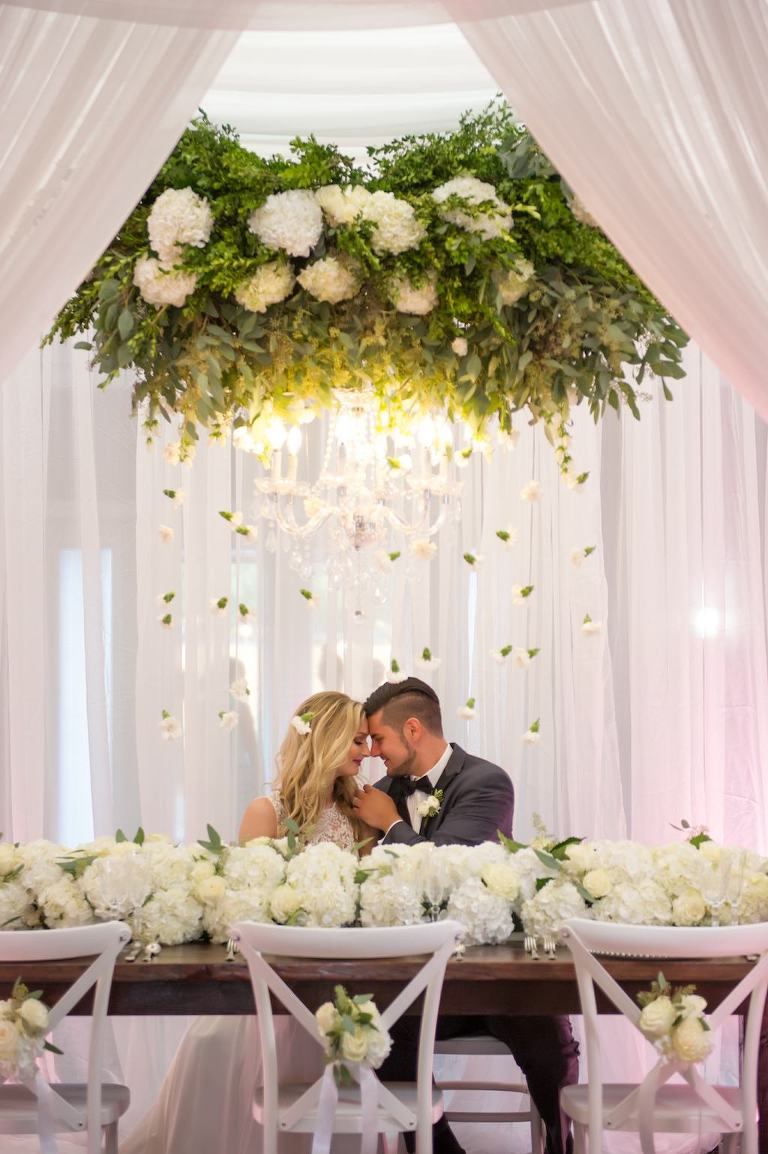 Elegant Southern White Wedding Reception Bride and Groom Portrait with Suspended White Florals with Hanging Organic Greenery, Low White Hydrangea Table Runner Garland Centerpiece, and White X Back Chairs with White Flowers and Ribbon at Wooden Farmhouse Table | Tampa Bay Wedding Planner Love Lee Lane | Tampa Event Rentals and Florist Gabro Event Services | Wedding Rentals A Chair Affair | Tampa Wedding Photographer Andi Diamond