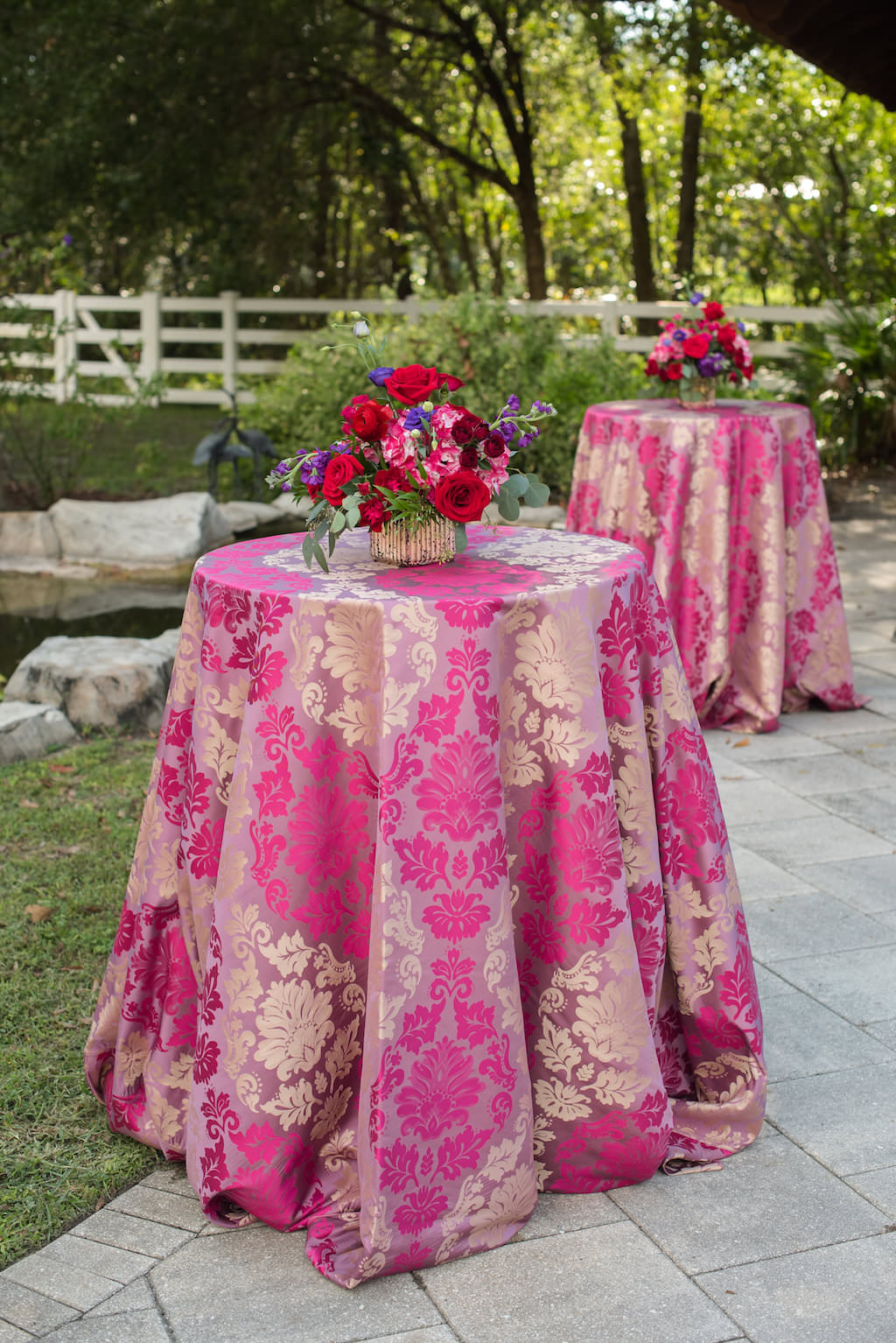 Colorful Outdoor Wedding Cocktail Reception Decor with Centerpieces with Red Roses, Pink, and Purple Flowers and Greenery on Pink and Gold Paisley Table Cloths | Northside Florist | Over the Top Rental Linens