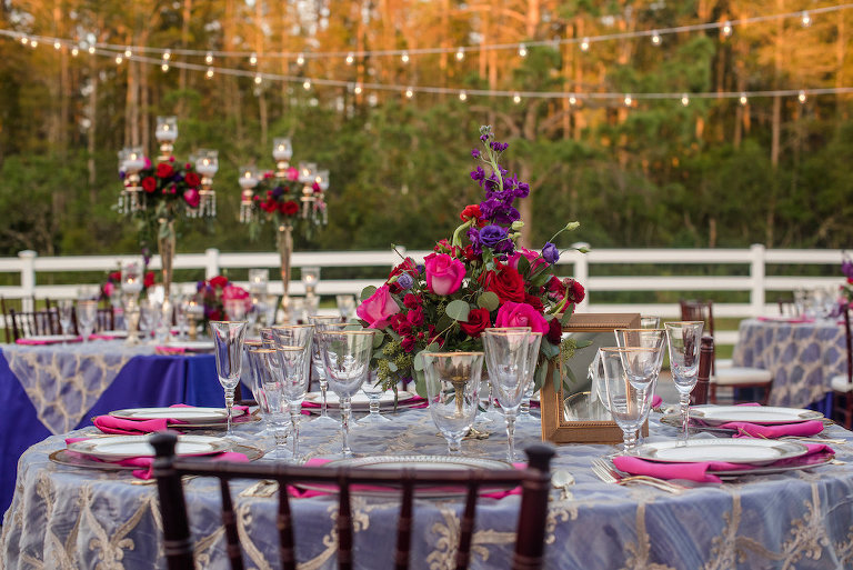 Elegant Southern Outdoor Wedding Reception Table Decor with Navy Blue, Vintage Lace, and Magenta Linens, Tall Gold Candelabra Centerpieces with Hurricane Lanterns, Red and Pink Roses, Purple Flowers and Greenery | Tampa Bay Wedding Planner Exquisite Events | Outdoor Tampa Bay Wedding Venue Southern Plantation Oasis | Northside Florist | Rentals by A Chair Affair