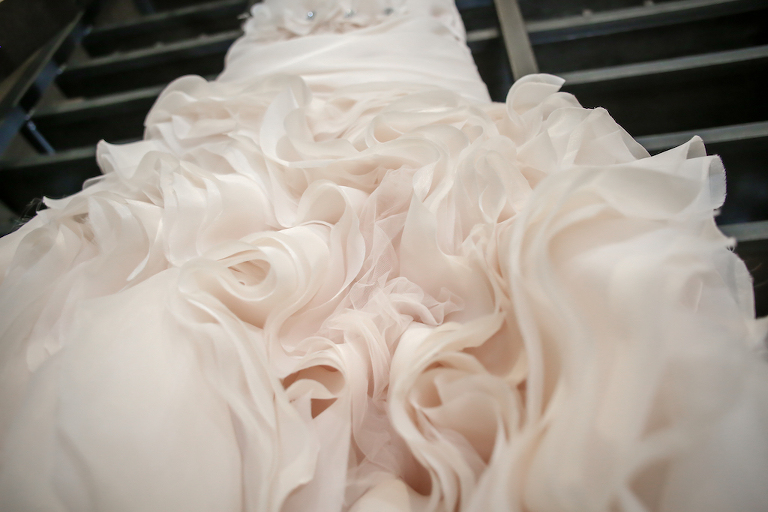 Detail Photo of Blush Ruffled Skirt of Wedding Dress on Hanger