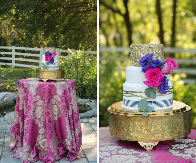 Colorful Three Tier Round White Wedding Cake with Gold Foil and Navy Stripes and Pearls on Gold Cake Stand, with Purple and Hot Pink Roses on Pink and Gold Paisley Tablecloth | Tampa Bay Wedding Cake Bakery A Piece of Cake | Over the Top Rental Linens