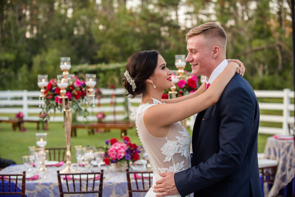 Luxurious Outdoor Tampa Bay Wedding Reception First Dance Portrait, with Navy Blue Linens, and Tall Gold Candelabra Centerpieces with Red, Magenta, and Purple Florals with Greenery | Tampa Wedding Photographer Caroline & Evan Photography | Tampa Bay Wedding Planner Exquisite Events