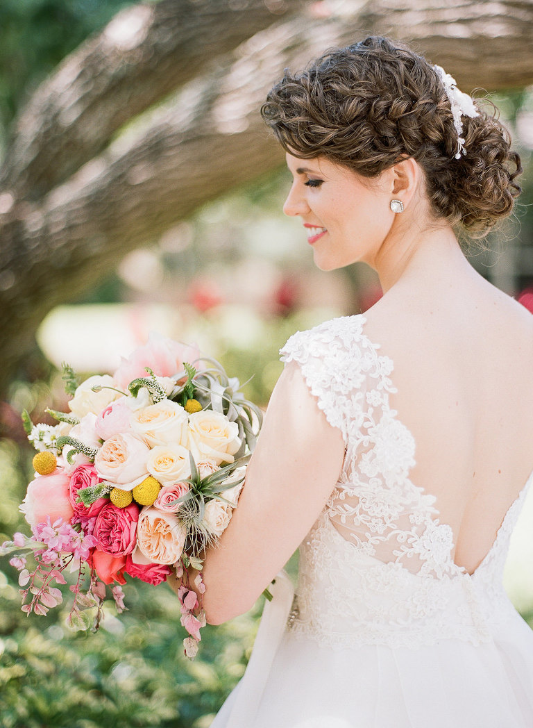 Outdoor Bridal Portrait wearing Lace Sleeve Open V Backed Paloma Blanca Wedding Dress with Peach, Blush, Magenta, and Yellow Bouquet with Greenery with Stylish Side Braid Wedding Updo Hair