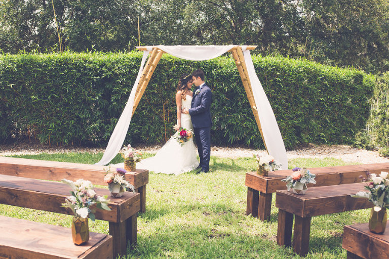 Natural Outdoor Garden Wedding Ceremony Bride and Groom Portrait with Magenta and Peach Rose with Greenery Bouquet, Sage Green Flower Arrangements in Gold Geodesic Vases on Rustic Wooden Pews, with Bamboo Ceremony Arch with White Draping | Tampa Bay Wedding Ceremony Venue Crowne Plaza Tampa