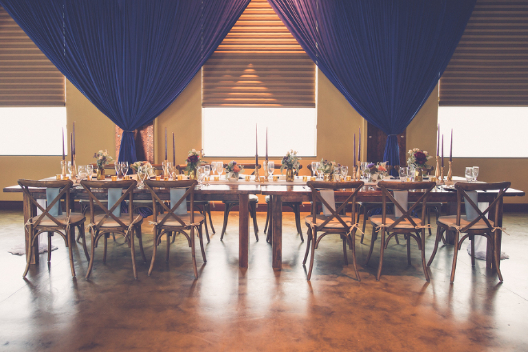 Natural Rustic Inspired Navy and Bordeaux Hotel Wedding Reception with Blue Draping, Wooden X Back Chairs, Long Wooden Tables, Low Floral Centerpieces and Tall Candles   Tampa Bay Modern Wedding Reception Venue Crowne Plaza Tampa   Tampa Farm Table Rentals A Chair Affair