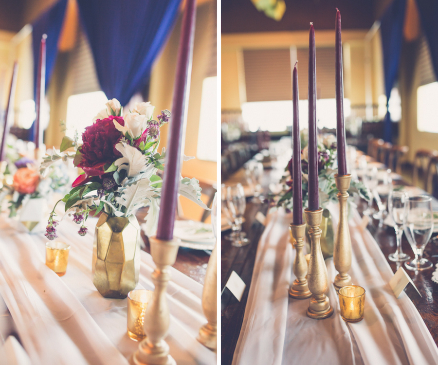 Elegant Modern Rustic Wedding Reception Table Decor with Tall Bordeaux Candles in Gold Candlestick Holders, Blush Table Runner, and small Magenta and White Floral with Greenery Centerpiece in Geodesic Gold Vase, Navy Blue Draping