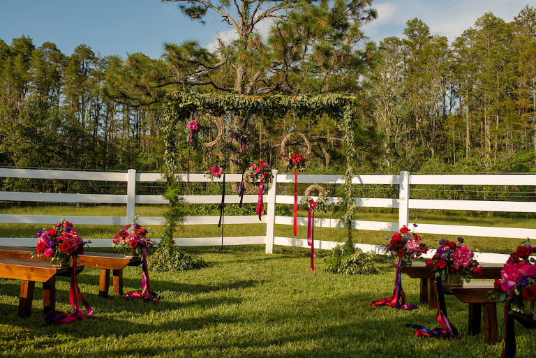 Outdoor Rustic Wedding Ceremony Decor with Wooden Benches, and Small Red, Purple, and Magenta Flowers with Pink and Purple Ribbon, and Rustic Ceremony Arch with Greenery Garland and Hanging Woven Branch Wreaths with Ribbon | Tampa Bay, Florida Wedding Venue Southern Plantation Oasis | Wedding Planner Exquisite Events | Northside Florist