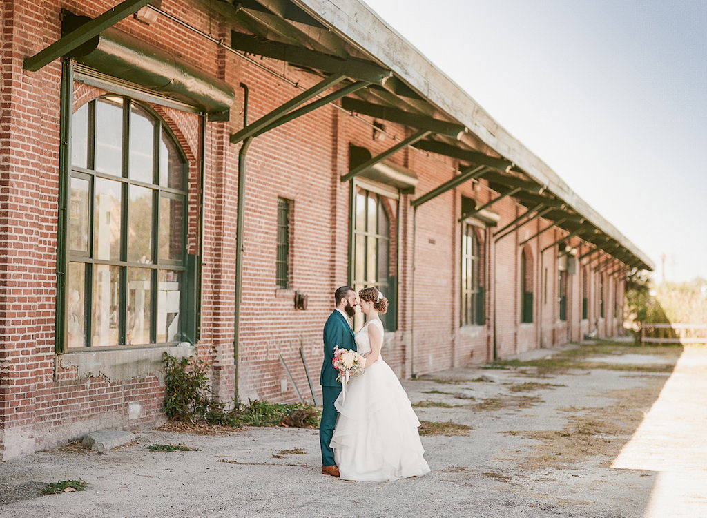 Bride and Groom Outdoor Industrial Wedding Portrait in Downtown St. Pete, Bride in Paloma Blanca Cathedral Train Wedding Dress with Coral Flower Bouquet, Groom in Teal Suit with Tropical Yellow and Pink Boutonniere