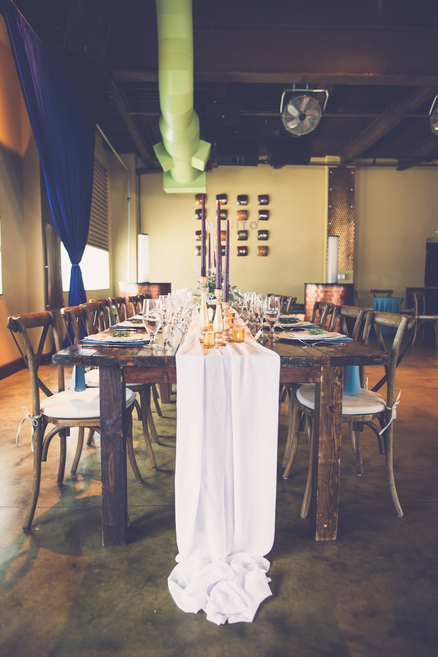 Boho Wedding Reception with Wooden Table, Wood X Back Chairs, Tall Burgundy Candles, Gold Accents, and Navy Blue Drapery | Tampa Bay Hotel Wedding Reception Venue Crowne Plaza Tampa | Tampa Farm Table Rentals A Chair Affair