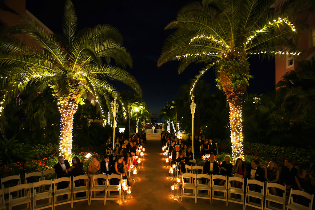 Outdoor Nighttime Courtyard Garden Wedding Ceremony with Folding White Chairs and Floating Votive Candles in Glass Cylinder Vases   St Pete Beach Historic Hotel Wedding Venue The Don Cesar