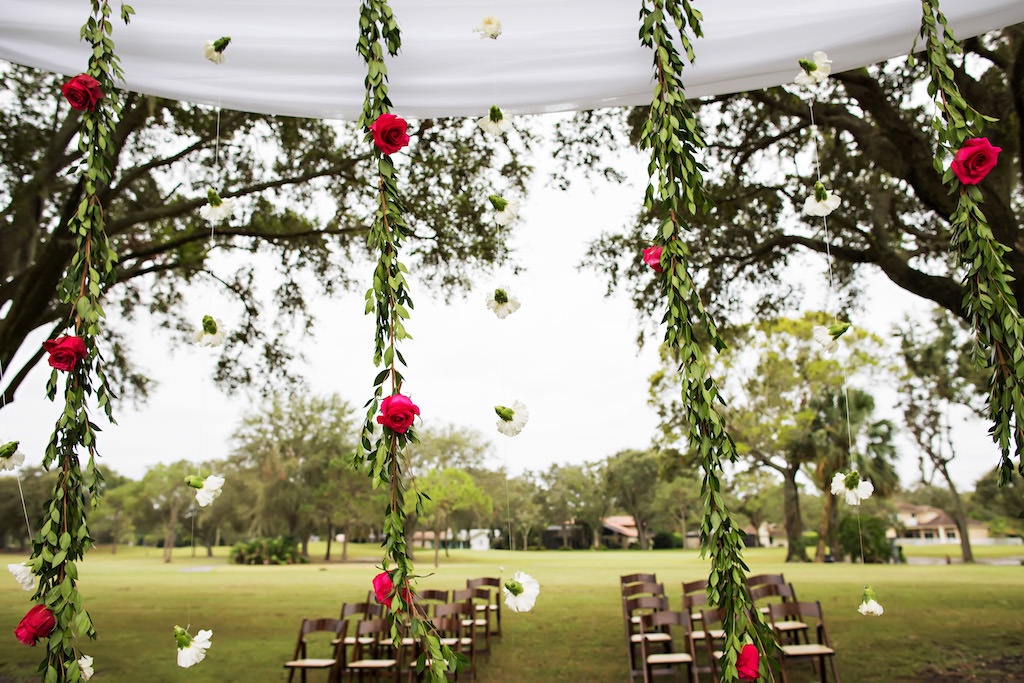 Outdoor Wedding Ceremony Decor with Arch with White Drapery and Hanging Greenery Garlands with Red Roses and White Flowers and Wooden Folding Chairs   Clearwater Golf Course Wedding Venue Countryside Country Club   Planner Special Moments Event Planning   Florist & Draping Gabro Event Services