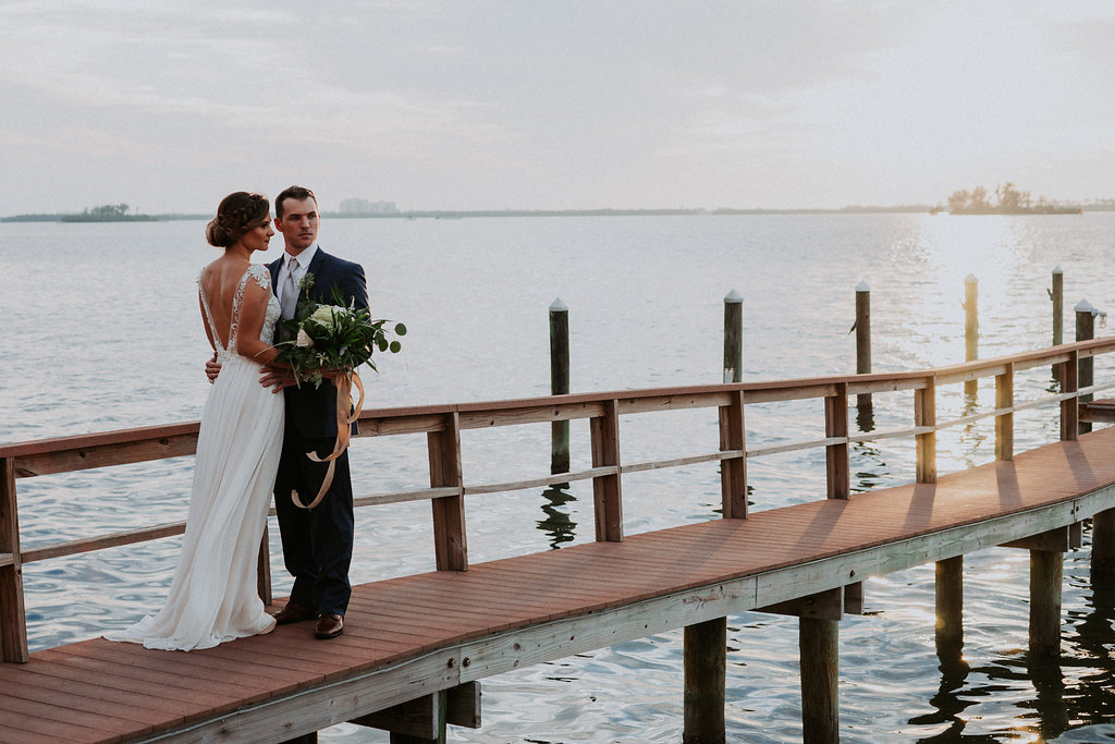 Outdoor Portrait on Waterfront Dock, Bride wearing Jeweled Lace Drop Back A Line Wedding Dress, Groom in Navy Suit with Silver Vest from Tampa Bay Formalwear Shop Nikki's Glitz and Glam | Dunedin, Florida Waterfront Wedding Venue Beso Del Sol Resort | Tampa Bay Wedding Photographer Grind and Press Photography