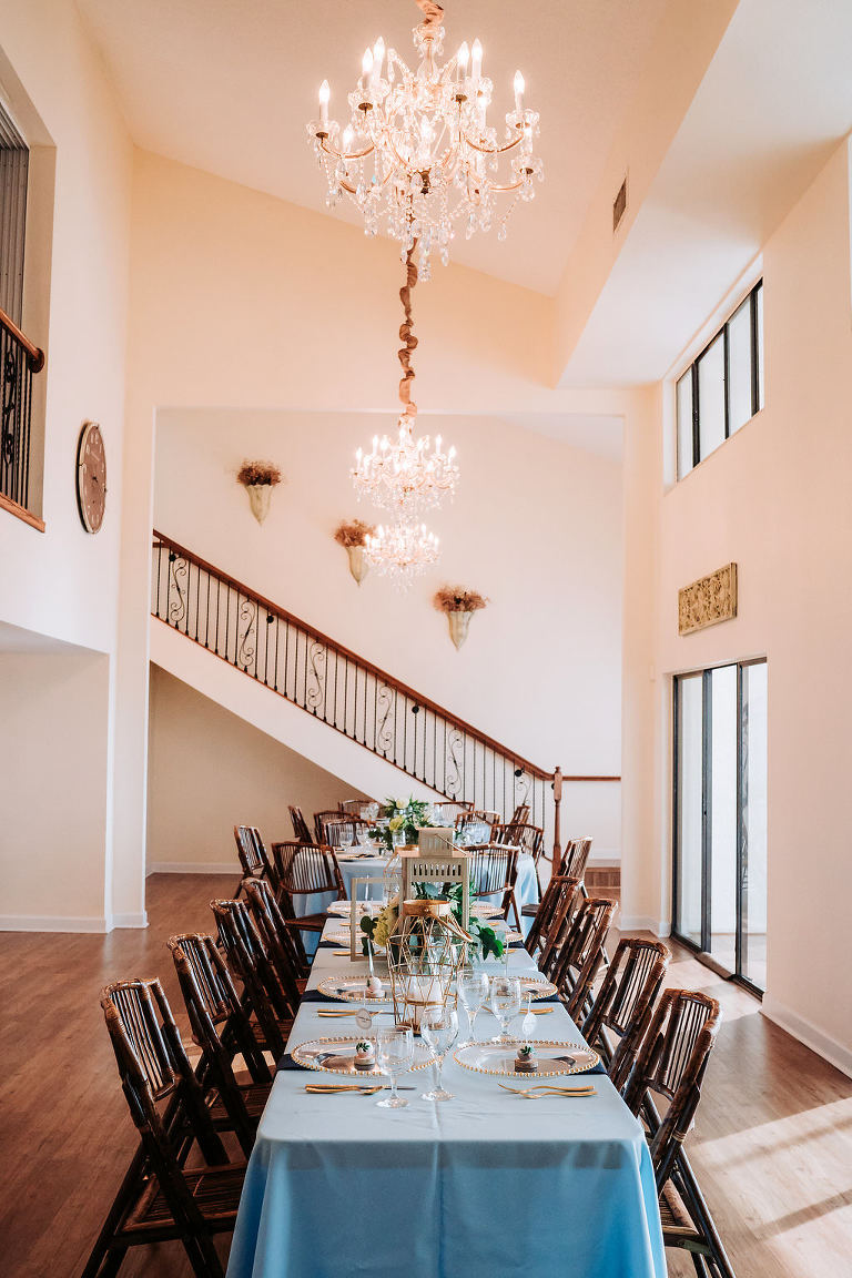 Coastal Glam Intimate Wedding Reception Decor with Long Feasting Table with Blue Linens, Low Natural Greenery and Hurricane Lantern Centerpiece, Bamboo Folding Chairs, and Gold Chargers and Flatware | Tampa Bay Waterfront Wedding Venue Beso Del Sol Resort | Coast to Coast Event Rentals