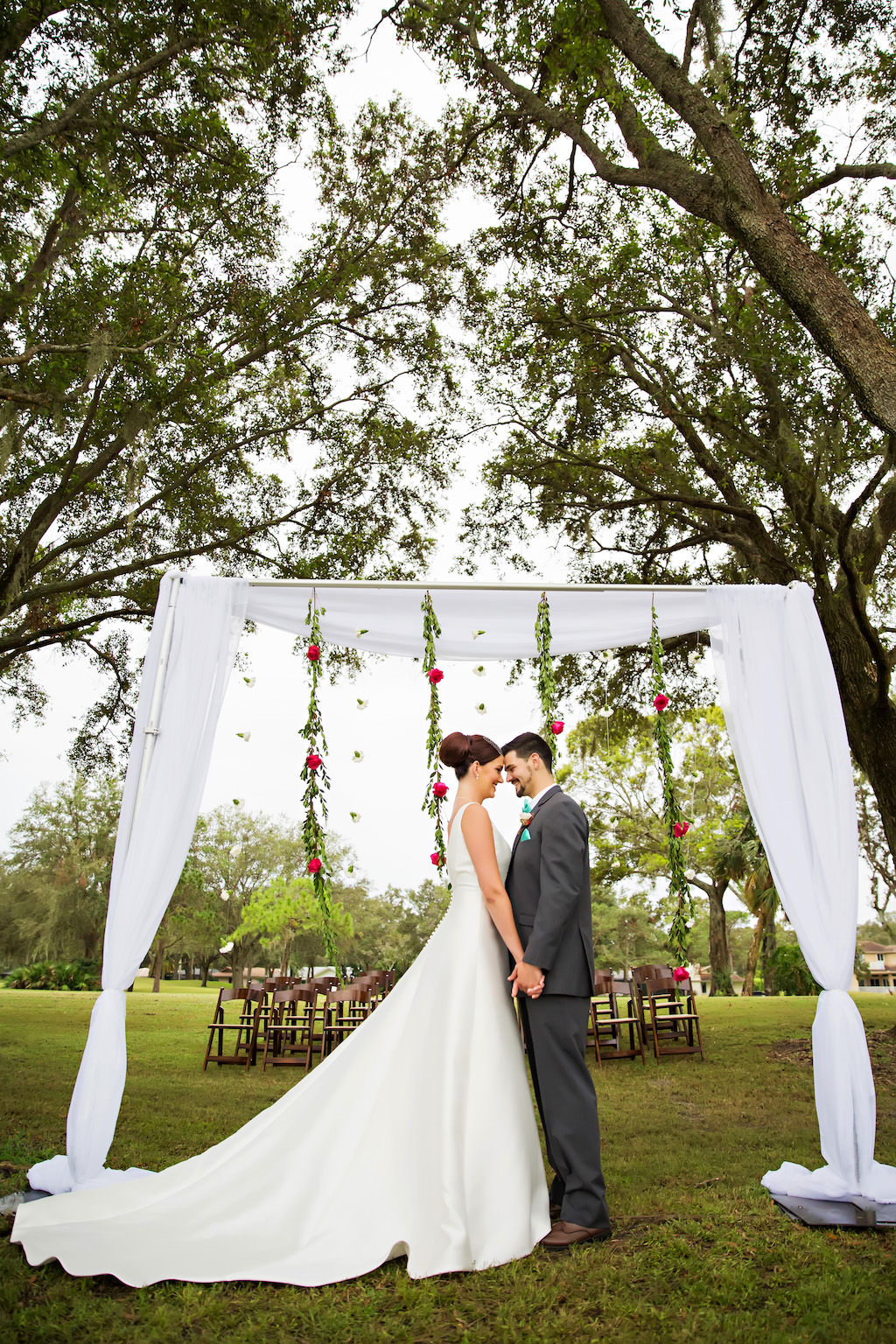 Outdoor Wedding Ceremony Portrait with Arch with White Drapery and Hanging Greenery Garlands with Red Roses and White Flowers and Wooden Folding Chairs   Clearwater Golf Course Wedding Venue Countryside Country Club   Planner Special Moments Event Planning   Florist and Decor Gabro Event Services