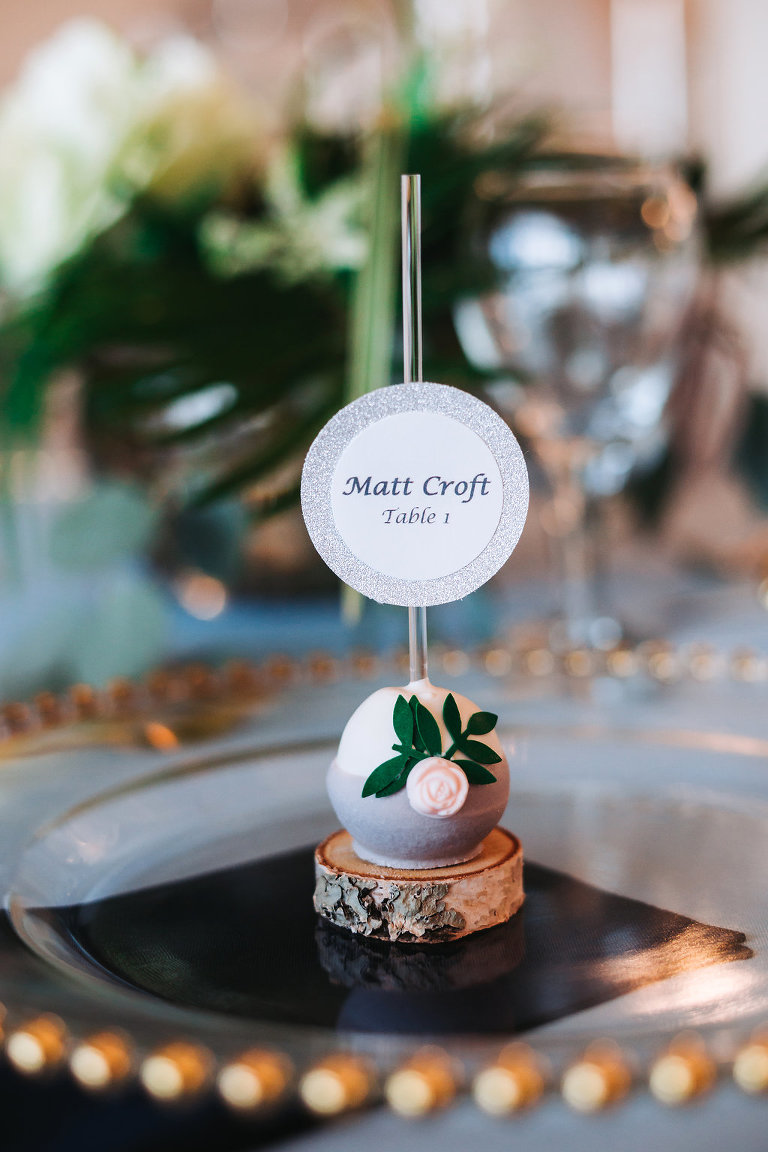 Elegant Coastal Glam Wedding Reception Cake Pop Wedding Favor and Name Card with Blue Icing and Rose Detail on Miniature Birchwood Stand on Gold Beaded Glass Charger | Tampa Bay Wedding Desserts Pop Goes the Party