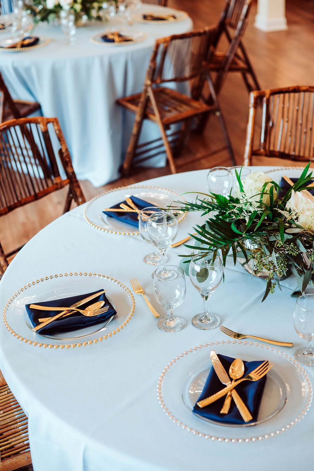 Elegant Coastal Tropical Wedding Reception Table Decor With Tropical Greenery Centerpiece Gold Flatware And Gold Beaded Glass Charger Light Blue Linen Tablecloth And Navy Blue Napkins Tampa Bay Wedding Linen Rentals