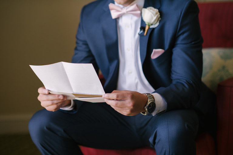 Groom Reading Letter from the Bride Wedding Portrait wearing Navy Suit, Blush Bowtie, and White Rose Boutonnière