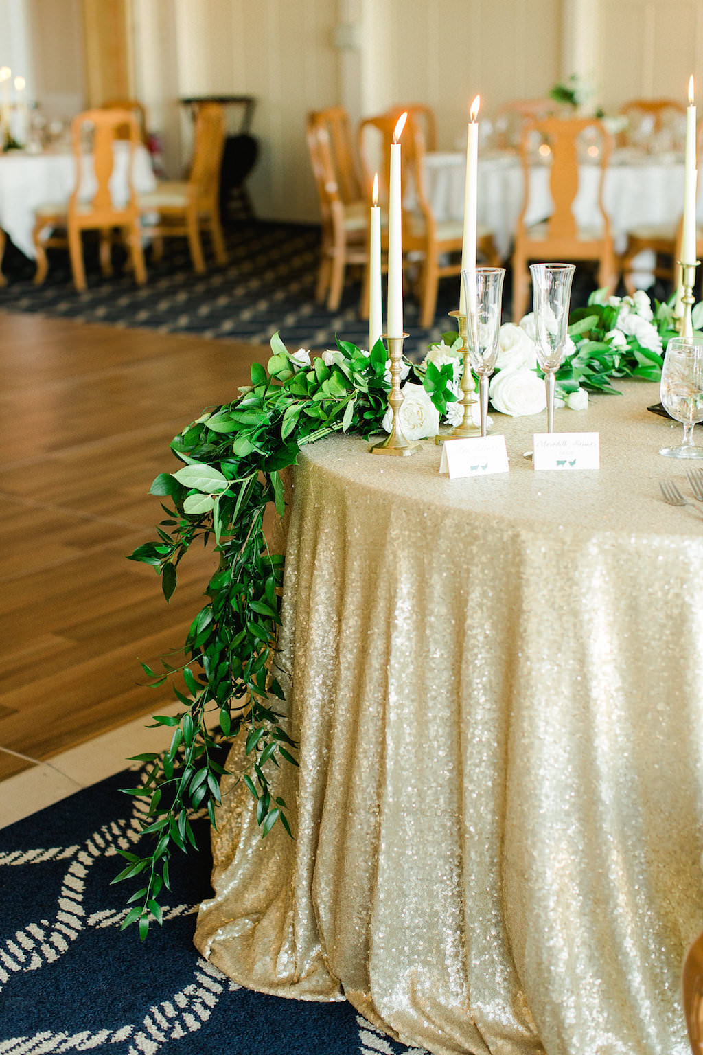 Old Florida Inspired White, Gold, and Green Wedding Reception Table Decor with Glitter Tablecloth, White Rose and Greenery Garland Centerpiece, and Elegant Candlestick holders | Clearwater Beach Wedding Reception Venue Carlouel Yacht Club | Tampa Bay Wedding Planner Glitz Events