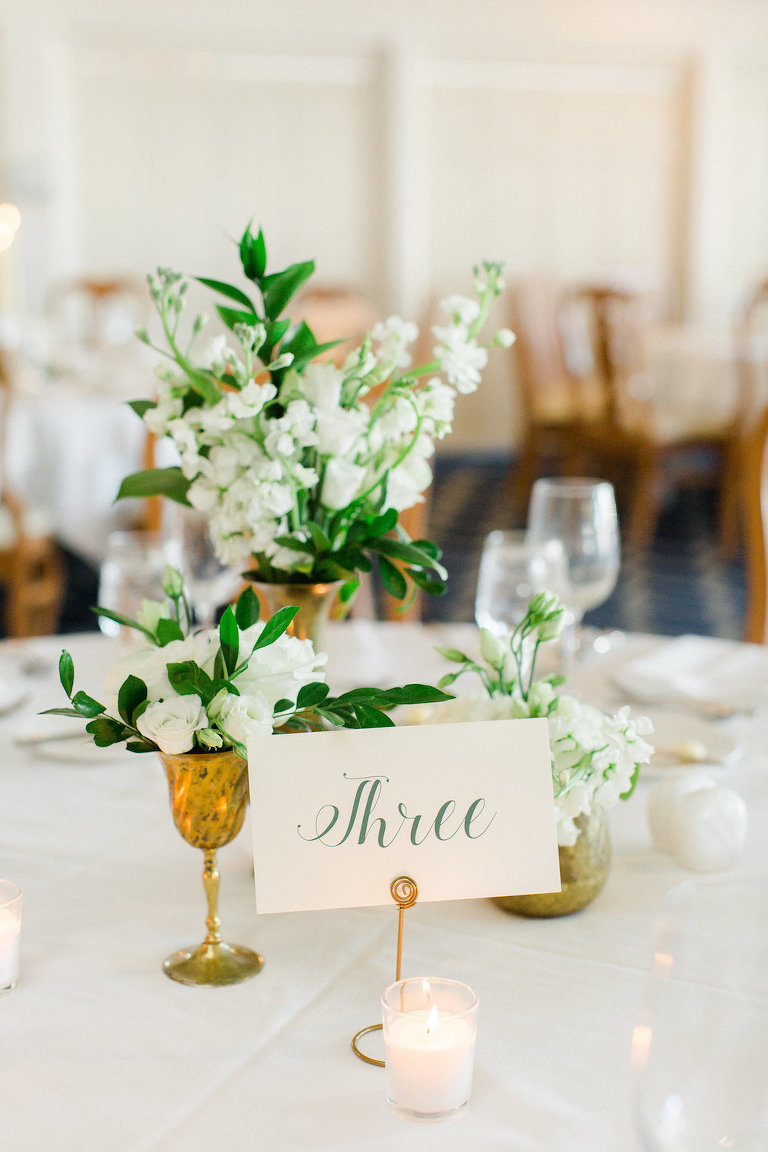 Old Florida Inspired Wedding Reception Table Decor with Small White Floral with Greenery Centerpieces in Mismatched Antique Gold Vases and Elegant Green on White Lettered Table Number Card | Tampa Bay Wedding Planner Glitz Events