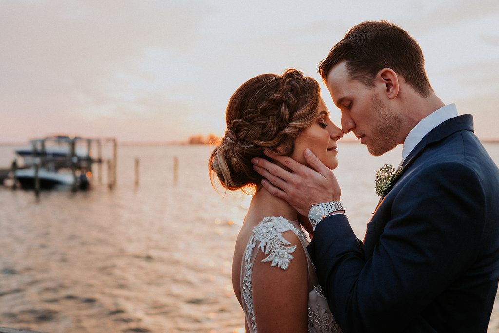 Outdoor Sunset Portrait on Waterfront Dock, Bride wearing Jeweled Lace Drop Back A Line Wedding Dress, Groom in Navy Suit with Silver Vest from Tampa Bay Formalwear Shop Nikki's Glitz and Glam | Dunedin, Florida Waterfront Wedding Venue Beso Del Sol Resort | Tampa Bay Wedding Photographer Grind and Press Photography | Hair and Makeup Femme Akoi