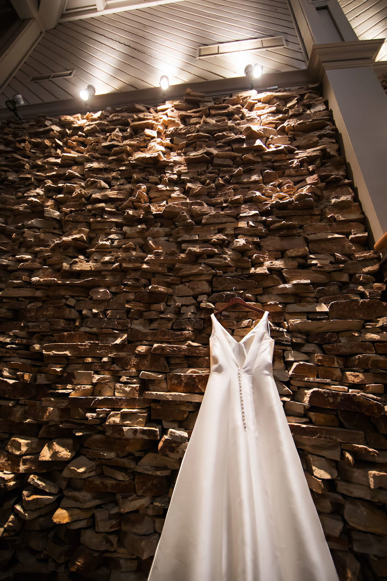 A Line Wedding Dress Hanging on Natural Brick Wall | Tampa Bay Bridal Boutique Truly Forever Bridal | Clearwater Wedding Venue Countryside Countryclub