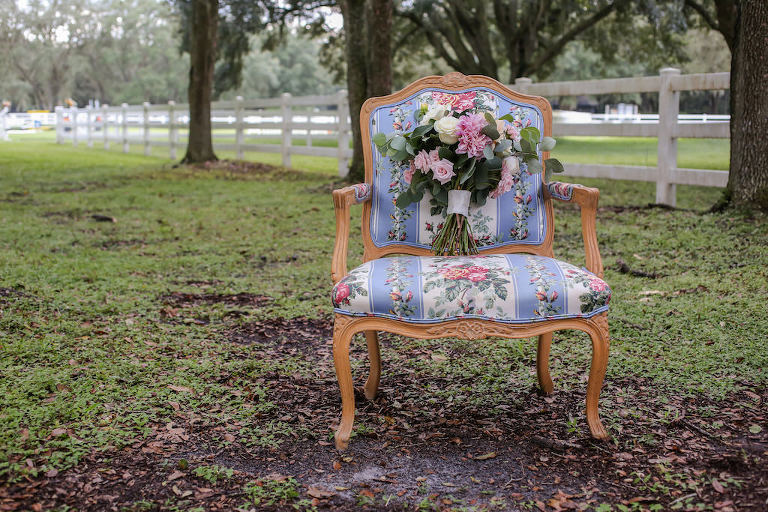 Pink and Ivory Roses with Greenery and White Ribbon Bridal Bouquet on Antique Upholstered Chair | Tampa Bay Farm Wedding Venue Lange Farm