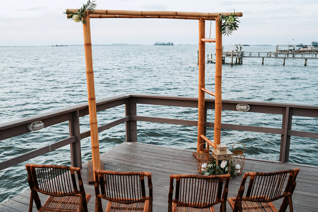 Intimate Coastal Themed Waterfront Wedding Ceremony Decor with Bamboo Arch and Folding Chairs, Vintage Hurricane Lanterns with Natural Tropical Greenery and White Florals | Tampa Bay Wedding Venue Beso Del Sol Resort