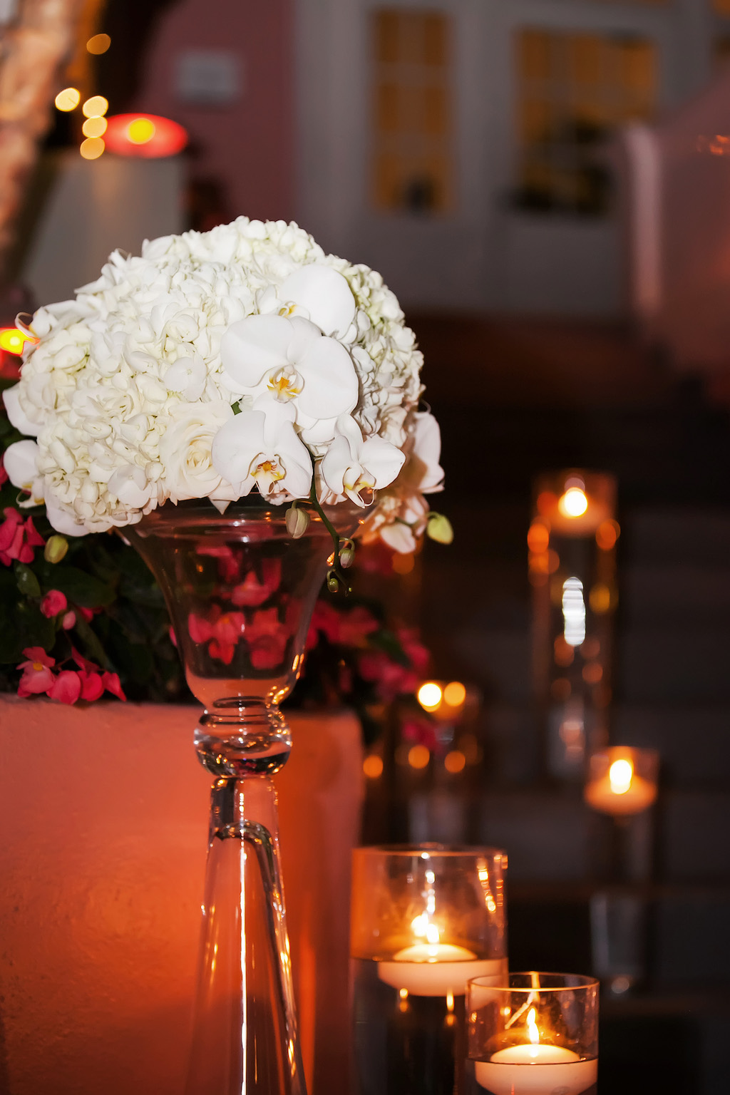Outdoor Garden Courtyard Wedding Ceremony Decor with White Hydrangea and Orchid Flowers in Tall Glass Vase with Floating Votive Candles in Hurricane Lanters