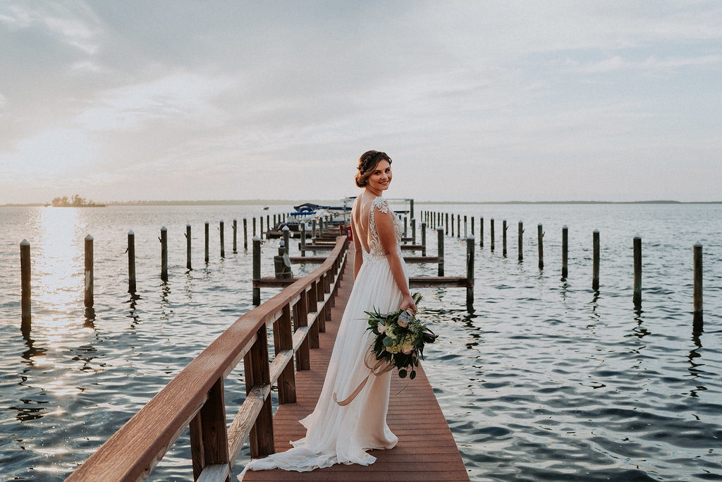 Outdoor Bridal Wedding Portrait on Dock, Bride wearing Jeweled Lace Drop Back A Line Wedding Dress from Tampa Bay Bridal Shop Nikki's Glitz and Glam, with Natural Coastal Greenery Bouquet | Dunedin, Florida Waterfront Wedding Venue Beso Del Sol Resort | Tampa Bay Wedding Photographer Grind and Press Photography | Hair and Makeup Femme Akoi