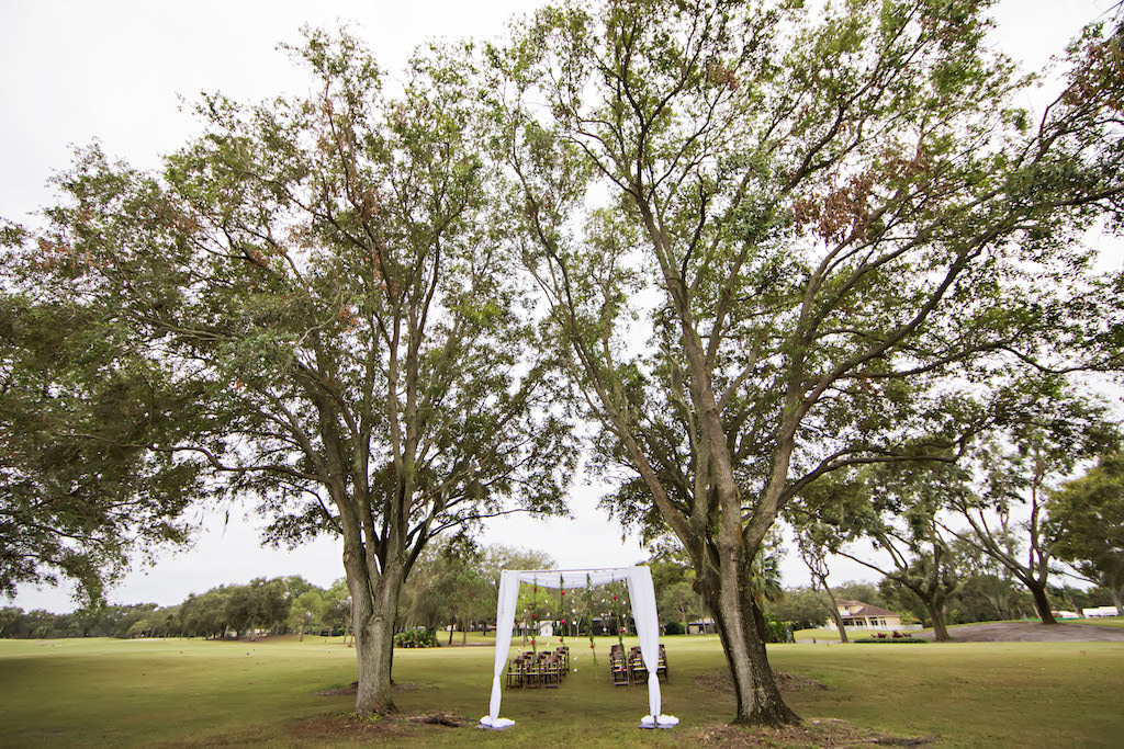 Outdoor Golf Course Wedding Ceremony Decor with Rectangular Arch with White Drapery and Hanging Flowers Under Large Tree   Clearwater Wedding Venue Countryside Country Club