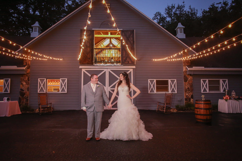 Outdoor Nighttime Bride and Groom Barn Wedding Portrait, Bride in Strapless Jeweled Mermaid Wedding Dress, Groom in Gray Suit with Blush Tie with Antique Barrels and String Lights | Tampa Wedding Photographer Lifelong Studios Photography | Rustic Barn Venue Lange Farm