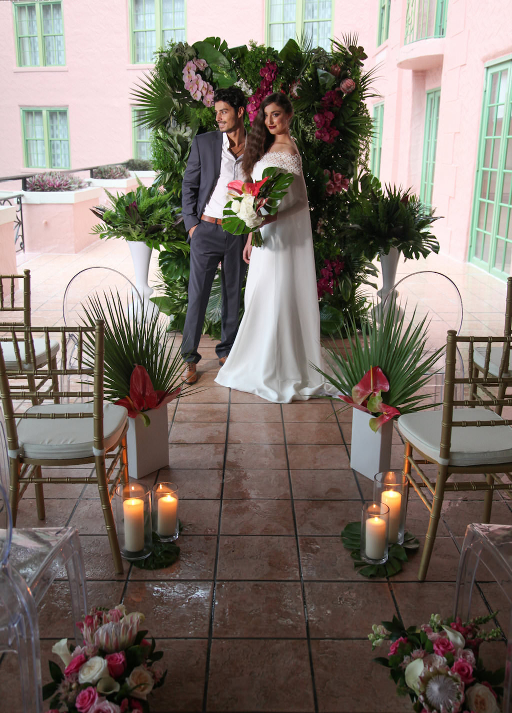 Intimate Hotel Courtyard Tropical Latin Cuban Inspired Wedding Ceremony, with Gold Chiavari Chairs, Tall Pillar Candles in Glass Hurricane Lanterns, Magenta, Pink and White Tropical Florals with Fern and Palm Frond Greenery, With Clear Acrylic Oval Backed Chairs   Tampa Bay Wedding Rentals A Chair Affair   Downtown St Pete Venue Vinoy Renaissance