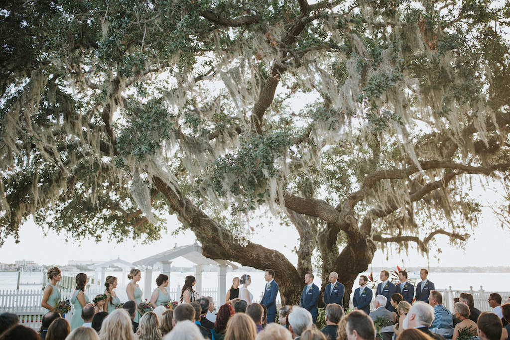 Outdoor Garden Wedding Ceremony with Folding White Chairs with Greenery and Sage Green Ribbon Florals and Wooden Unplugged Ceremony Welcome Sign with White Painted Script | Bradenton Wedding Venue Palmetto Riverside Bed and Breakfast | Sarasota Wedding Planner Jennifer Matteo Event Planning