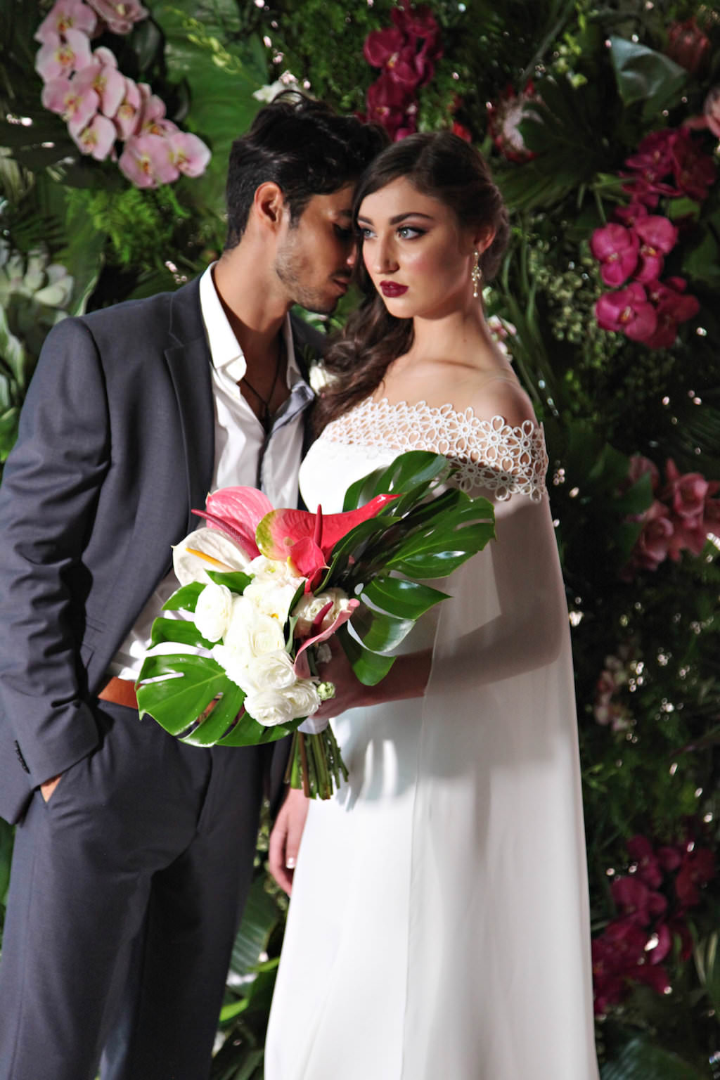 Tropical Wedding Ceremony Portrait, Bride in Lace Off The Shoulder Caped Ines Di Santo Wedding Dress, with Pink and White Lily and Monsterra Palm Frond Bouquet, with Orchid and Fern Greenery Backdrop   Latin Inspired Cuban Havana Nights Wedding