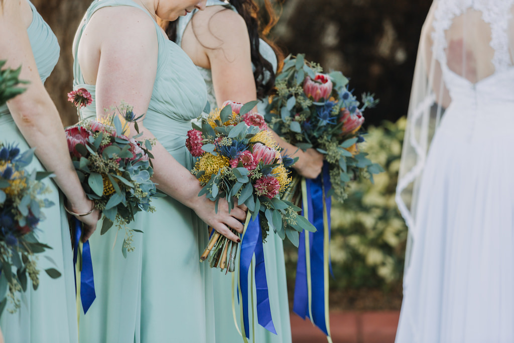 Mediterranean Blue and Green Garden Wedding Ceremony Portrait, Bridesmaids in Sage Azazie Dresses with Pink, Yellow and Greenery Bouquets with Cobalt Ribbons