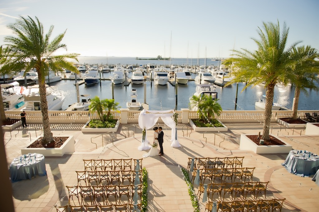 Outdoor Waterfront French Countryside Inspired Wedding Ceremony with Wooden Cross Back Chairs with Wide Light Blue Ribbon, Greenery Garland Aisle, and White Draped Ceremony Arch | Tampa Bay Wedding Planner Kelly Kennedy Weddings and Events | Tampa Waterfront Outdoor Wedding Venue Westshore Yacht Club