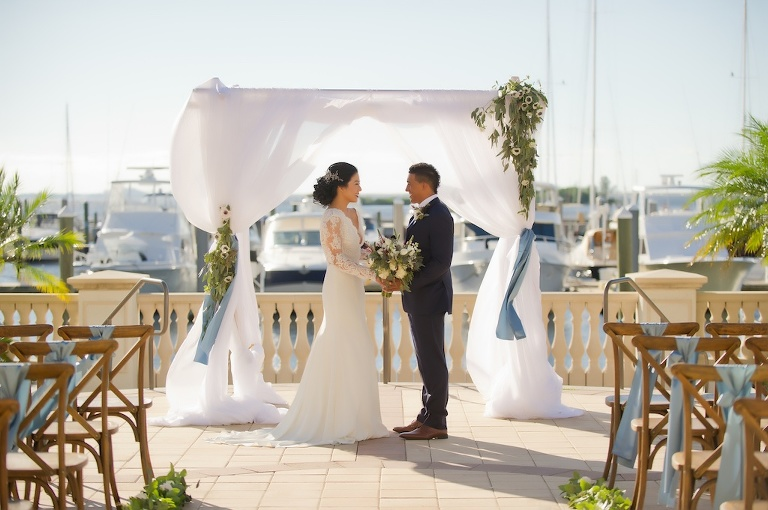 Outdoor Waterfront French Countryside Inspired Wedding Ceremony with Wooden Cross Back Chairs with Wide Light Blue Ribbon, Greenery Garland Aisle, and White Draped Ceremony Arch with White Anemone and Greenery Flowers | Tampa Bay Wedding Planner Kelly Kennedy Weddings and Events | Tampa Waterfront Outdoor Wedding Venue Westshore Yacht Club | Tampa Wedding Photographer Andi Diamond Photography